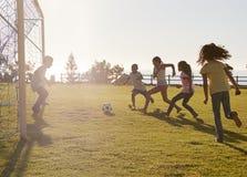 Ungar som spelar fotboll i en parkera, en i mål, sidosikt Arkivfoton
