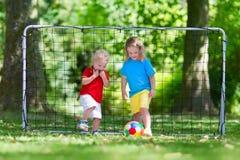 Ungar som spelar fotboll i skolgård Royaltyfri Bild