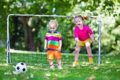 Ungar som spelar fotboll i skolgård Arkivfoton