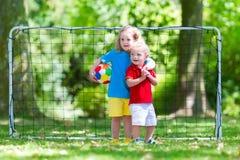 Ungar som spelar fotboll i skolgård Arkivbild