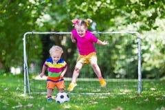 Ungar som spelar fotboll i skolgård Royaltyfria Bilder