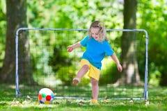 Ungar som spelar fotboll i skolgård Royaltyfria Foton