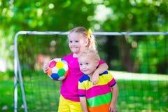 Ungar som spelar fotboll i skolgård Royaltyfri Fotografi