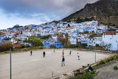 Ungar som spelar fotboll i staden av Chefchaouen i Marocko Arkivbild