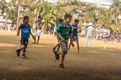 Ungar som spelar fotboll på Mumbai jordning Arkivfoton
