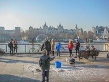 Ungar som spelar i en gata, visar med såpbubblor, att hålla ögonen på för folk arkivbild