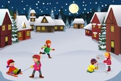 Ungar som spelar i en vinterunderland Arkivfoto