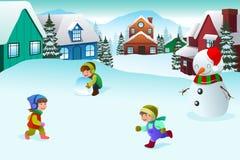 Ungar som spelar i en vinterunderland Arkivfoton