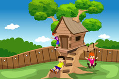Ungar som spelar i ett trädhus Arkivbilder