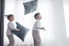 Ungar som spelar i föräldersäng Barn vaknar upp i soligt vitt sovrum Pojke- och flickalek, i att matcha pyjamas sleepwear arkivbilder