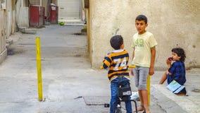 Ungar som spelar i gatan av Muharraq, Bahrain arkivfoton