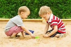 Ungar som spelar i sand, utomhus- fritid för två barnpojkar i sandlåda royaltyfri bild