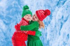 Ungar som spelar i snöig vinterskog Arkivfoto