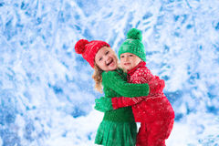 Ungar som spelar i snöig vinterskog Royaltyfri Bild