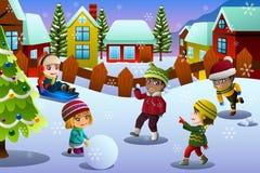 Ungar som spelar i snön under vintersäsong Arkivfoto
