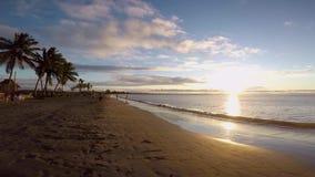 Ungar som spelar i stranden under den härliga solnedgången i den Nadi stranden fijiansk ö arkivfilmer