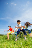 Ungar som spelar leken och, sitter snabbt på stolar utanför Royaltyfri Fotografi