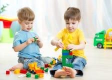 Ungar som spelar leksaker i lekrum på barnkammaren royaltyfria foton