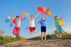 Ungar som spelar med ballonger Arkivbild