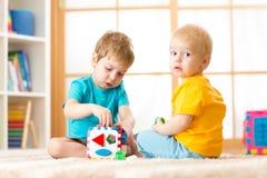 Ungar som spelar med den logiska leksaken på mjuk matta i barnkammareroomordagis Barn som ordnar och sorterar former eller format Royaltyfria Bilder