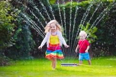 Ungar som spelar med den trädgårds- spridaren Fotografering för Bildbyråer