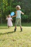 Ungar som spelar med en ballong Arkivfoton