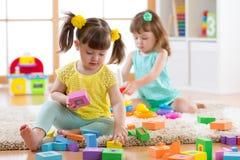 Ungar som spelar med färgrika kvarterleksaker Barn som hemma bygger torn eller daycaremitten Bildande barnleksaker för den förträ royaltyfri bild