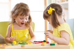 Ungar som spelar med färgrika kvarterleksaker Två barnflickor hemma eller daycaremitt Bildande barnleksaker för förträning och so Royaltyfria Bilder