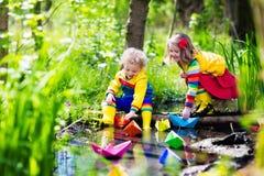 Ungar som spelar med färgrika pappers- fartyg i en parkera arkivbilder