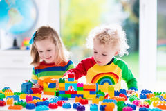 Ungar som spelar med färgrika plast- kvarter Royaltyfri Bild