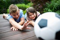 Ungar som spelar med fotboll på bryggan Royaltyfri Bild