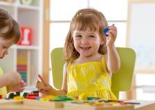 Ungar som spelar med hemmastadda utvecklings- leksaker eller dagis- eller daycaremitten royaltyfri bild