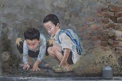 Ungar som spelar med marmorväggmålningen av Kwai Chai Hong royaltyfri bild