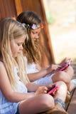 Ungar som spelar med minnestavlan och, ilar telefonen utomhus. Arkivbild