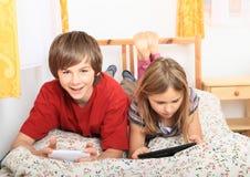 Ungar som spelar med minnestavlan och smartphonen Arkivfoton