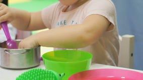 Ungar som spelar med plast- barns bordsservis stock video