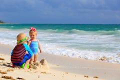 Ungar som spelar med sand på den tropiska stranden royaltyfri foto