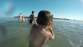 Ungar som spelar med strandvattenvapnet lager videofilmer