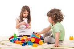 Ungar som spelar med tegelstenleksaker Fotografering för Bildbyråer