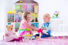 Ungar som spelar med välfyllda djur och dockhuset Royaltyfri Fotografi