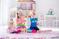 Ungar som spelar med välfyllda djur och dockhuset Royaltyfri Foto
