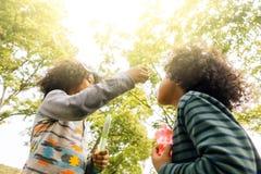 Ungar som spelar med vänner Ungar som spelar blåsa bubblor royaltyfri fotografi