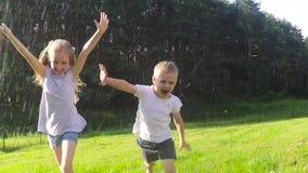 Ungar som spelar med vattenslangen
