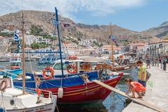 Ungar som spelar nära en fiskebåt på den grekiska öhydraen Arkivbilder