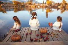 Ungar som spelar nära sjön i höst Arkivfoto