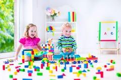 Ungar som spelar på daghem med träleksaker Arkivfoton