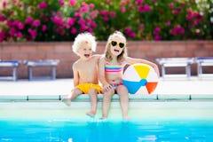 Ungar som spelar på den utomhus- simbassängen Fotografering för Bildbyråer