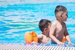 Ungar som spelar på den utomhus- simbassängen arkivbilder