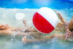 Ungar som spelar på den utomhus- simbassängen Lilla flickan och pojken spelar och simmar i hemmet blåst upp pöl arkivfoton