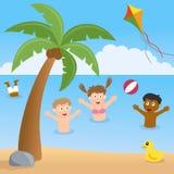 Ungar som spelar på en strand med palmträdet Arkivfoto